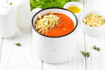 Tomato cream soup in white mug, red hot soup in cup with fragrant breadcrumbs,  olive oil. Vegetarian vegetable lunch on wooden background