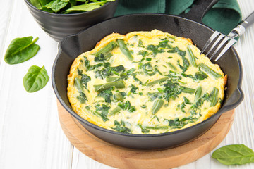 Omelet with spinach and green beans, healthy food. Egg and milk Frittata, delicious Breakfast. In black frying pan on white wooden background