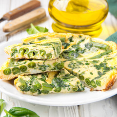 Omelet with spinach and green beans, healthy food. Egg and milk Frittata, delicious Breakfast on white wooden background