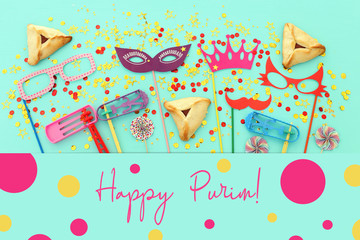 Purim celebration concept (jewish carnival holiday) over mint wooden background. Top view, Flat lay