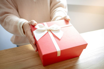 hands of woman present a red gift box, surprise for valentine concept.