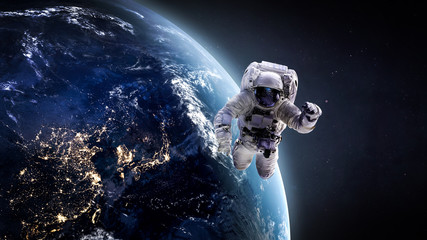 Nightly Earth and astronaut in the outer space. Abstract wallpaper. City lights on planet. Spaceman. Elements of this image furnished by NASA