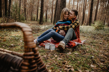 Smiling young couple embracing while sitting in forest