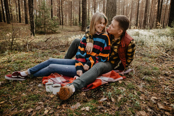 Smiling young couple sitting in forest