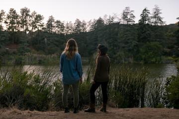 Female friends standing near lake