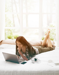 Woman lying on bed and connecting with her laptop