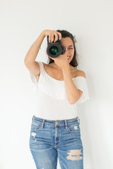 Smiling female photographer taking picture with camera against white background