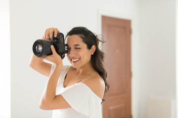 Smiling female photographer taking picture with camera
