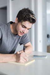 Young man writing on book