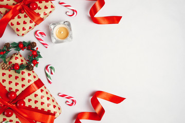Overhead view of gifts, candy cane and candle on white background