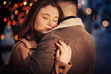 Young happy attractive couple embracing on illuminated city street at winter time.