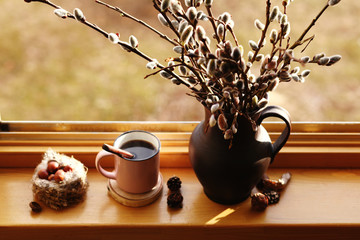 a cup of coffee and willow branches in the jug and the bird nest on the windowsill at sunny day