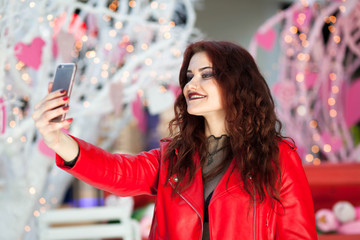 Happy young girl in a red jacket makes selfie