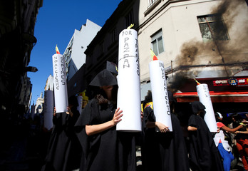 """A demonstrator in black robe holds a candle with the inscription """"for peace, bread, and jobs"""" during a protest against the increase of public rates, in Buenos Aires"""