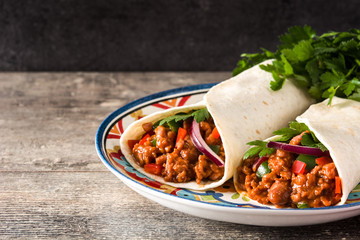 Typical Mexican burrito wrap with beef, frijoles and vegetables  on wooden table. Copyspace