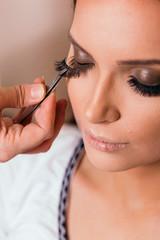 Make up artist putting artificial eyelashes