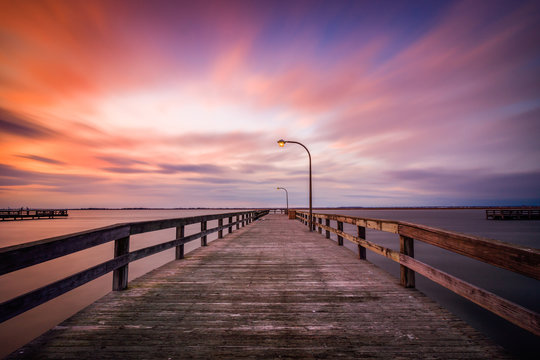Beautiful colorful clouds streaking over a pier at sunset. Dramatic coastal scene with no people. Long Island New York.
