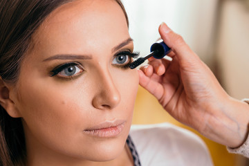 Make up artist putting mascara on female client's eyelashes