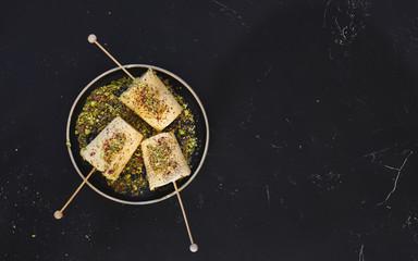 Fototapeta Saffron pistachio cream kulfi, traditional Indian dessert, ready to eat. Top view, blank space obraz