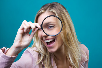 Cheerful pretty girl looking through magnifying glass isolated over blue background.