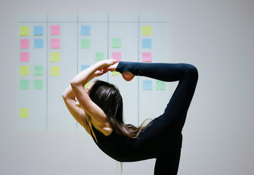 Girl symbolizes flexibility of agile project management approach: she is doing gymnastics element on the background of scrum task board