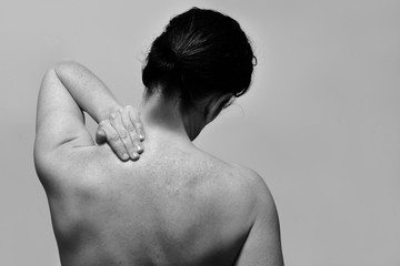 middle-aged woman with pain in the upper part of the spine