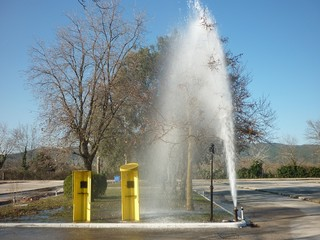 Damaged fire hydrant spraying fresh water at an empty park in a sunny day at a park of a city two old yellow telephone boxes nearby trees at the background and blue sky