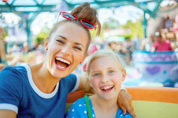 mother and child tourists in theme park enjoying attraction