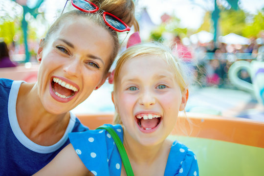 smiling mother and child tourists in theme park having ride