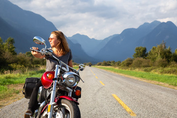 Woman riding a motorcycle on a scenic road surrounded by Canadian Mountains. Taken in Pitt Meadows, Greater Vancouver, BC, Canada.