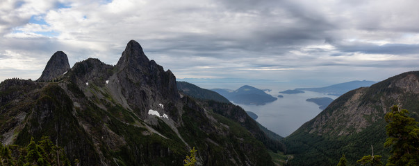 Beautiful panoramic view of The Lions Peaks and Howe Sound during a vibrant summer sunrise. Located near Vancouver, BC, Canada.