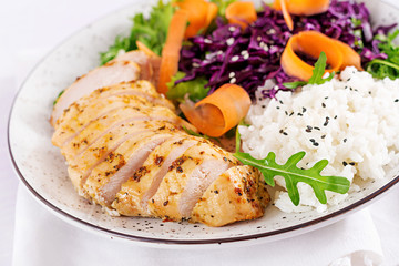 Healthy salad. Buddha bowl dish with chicken fillet, rice,  red cabbage, carrot, fresh lettuce salad and sesame. Healthy balanced eating.