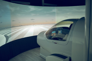 Side view of male trainee flying flight simulator seen through windshield