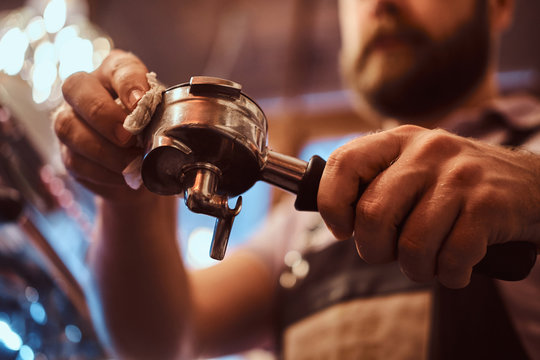 Low angle photo of a barista cleans the portafilter before preparing the cappuccino in a coffee shop or restaurant. Close-up