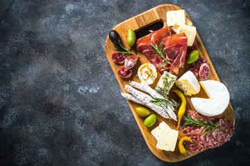 Antipasto board with sliced meat, ham, salami, cheese, olives and red wine.
