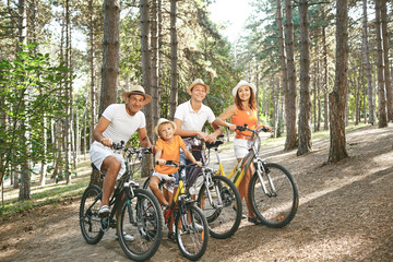 Happy family on bicycles for a walk in park.