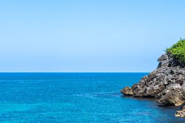 Caribbean island cliff side coastline, epic aqua ocean water. Tropical vacation scenery.