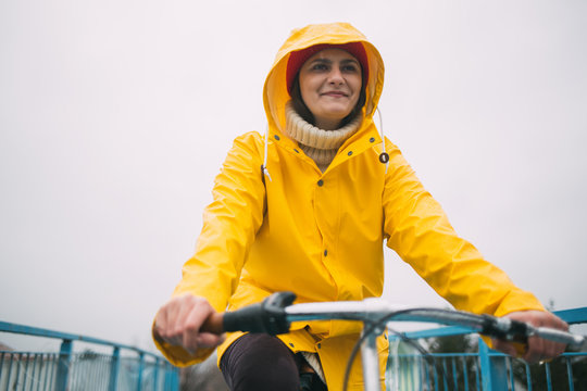 Young woman riding bicycle and wearing raincoat