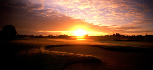 Panoramic view of golf course at sunrise.
