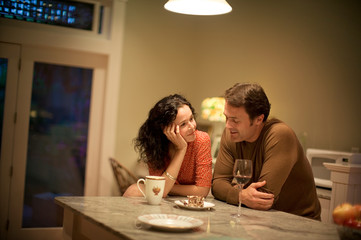 Mid-adult couple happily sitting and talking in their kitchen.