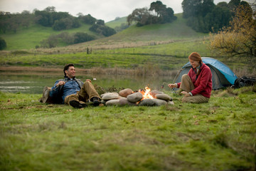 Mid-adult couple sitting beside a camp fire.