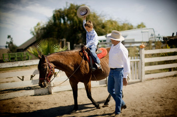 boy rides horse as father watches