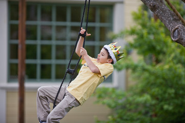 Young boy swinging on a rope ladder while wearing a crown and playing in the back yard.