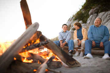 Mature couple sitting with their teenage grandson beside a bonfire on a beach.