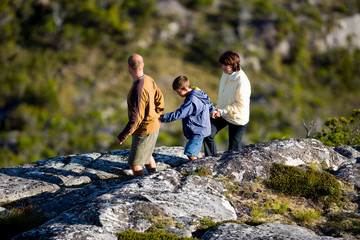 Mid-adult couple and their young son climbing a hill.