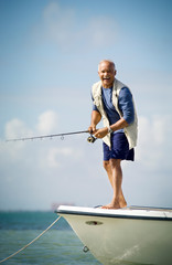Portrait of a mature adult man fishing off the edge of a boat.