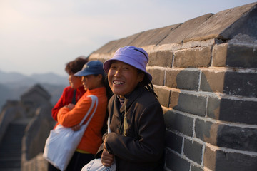 Three women huddled against a wall at the Great Wall Of China.