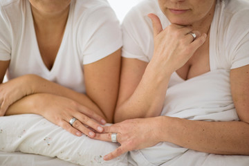 Silver rings on the hands of a lesbian couple.