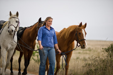 Young woman leading three horses along a beach.