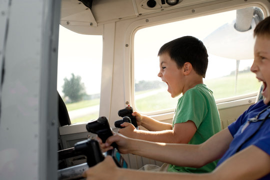 Two young boys pretending to fly a plane while sitting together inside the cockpit of a small airplane.